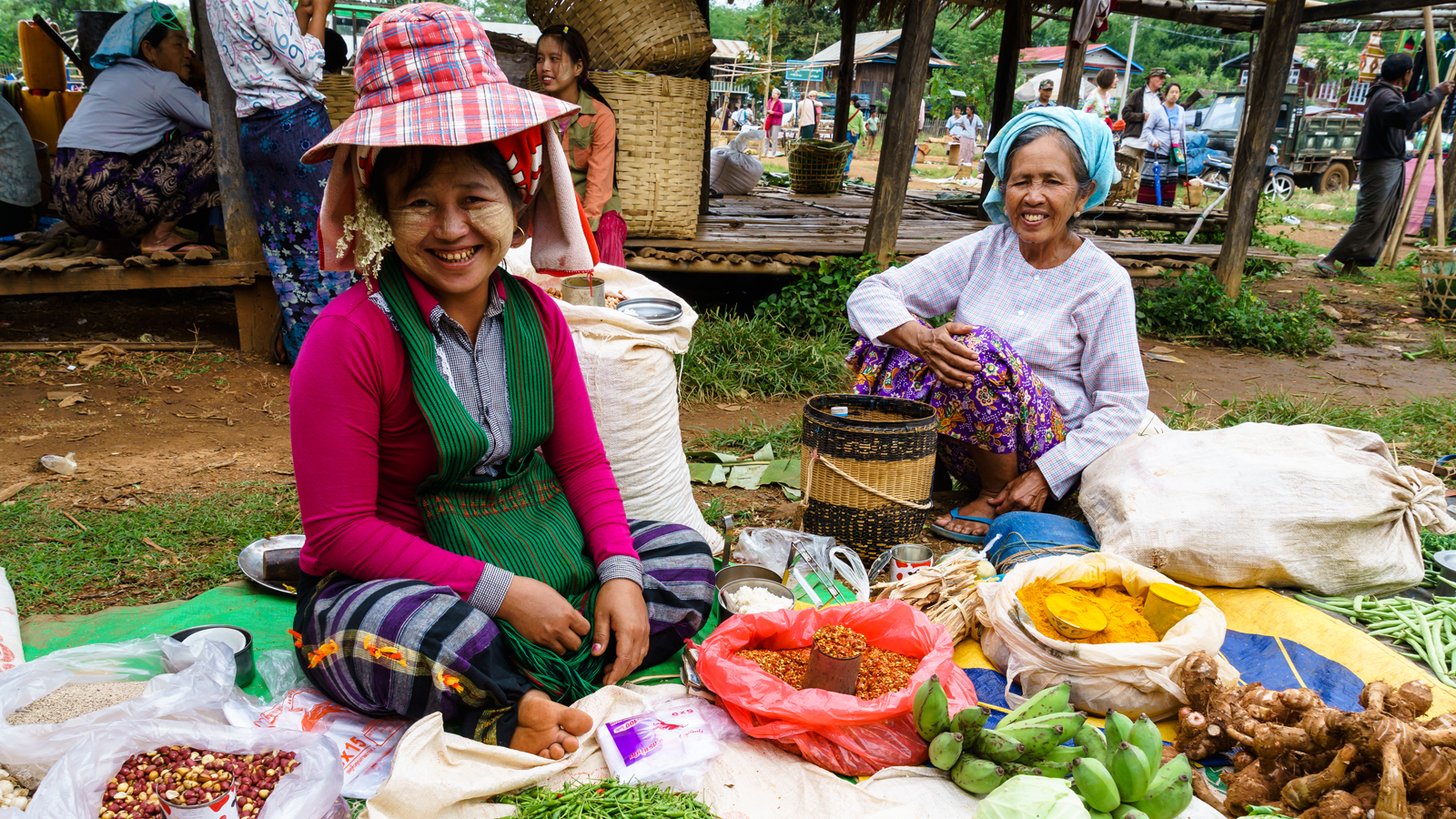 Woman smiling among many artisan-crafted hats