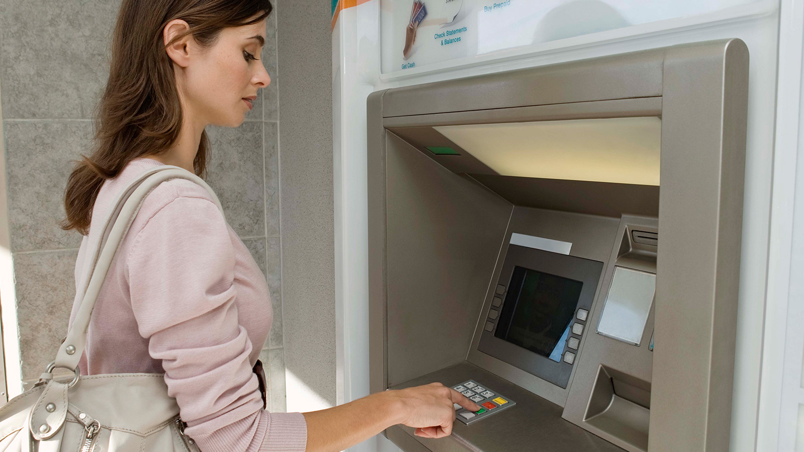 Woman standing at ATM.