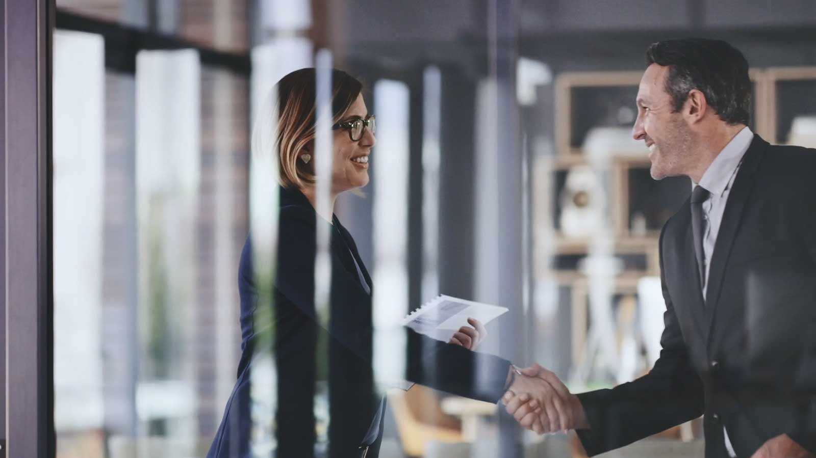 A business woman and business man exchanging a handshake in an office.